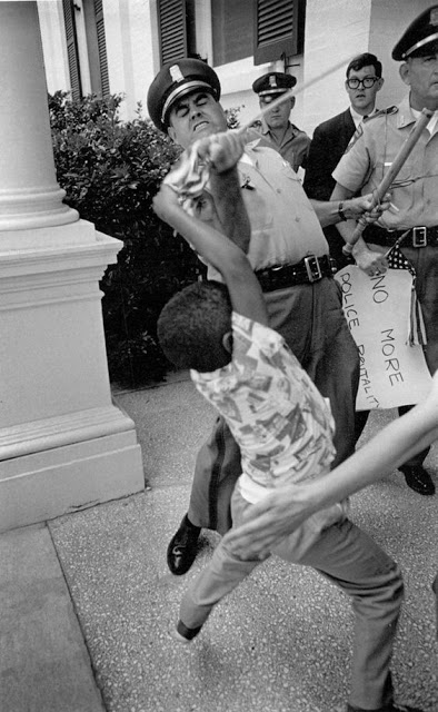 Anthony Quinn, five-years-old, attempts to keep his small American Flag while U.S. Highway patrolman Huey Krohn grabs it out of Anthony's hand. 1965. Photo by Matt Herron