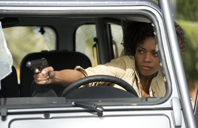 Naomi Harris as Eve Moneypenny taking aim behind the wheel