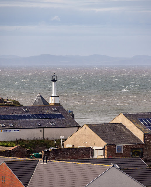 Photo of looking over the rooftops to Maryport Lighthouse and the Solway Firth
