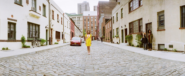 a panoramic photo of Liz on the cobblestone NYC street