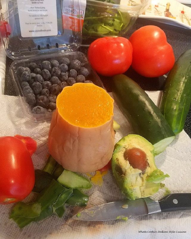 this is a photo of all the vegetables to make in this salad recipe. There is butternut squash, tomatoes, blueberries, avocado and cucumbers in this photo