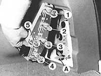Открыв багажник с помощью отвертки повернуть стопор крепления и снять кожух заднего фонаря