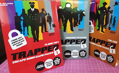 All 3 new Trapped escape room games in packaging laid out on table