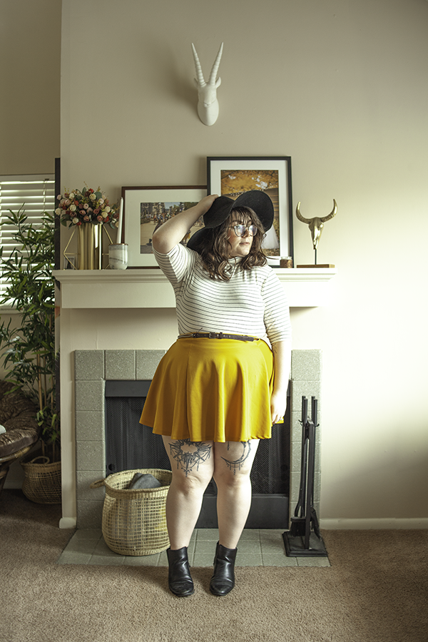 An outfit consisting of a black wide brim hat, a 3/4 sleeve white and black turtleneck top tucked into a mustard yellow mini skater skirt with black Chelsea boots.