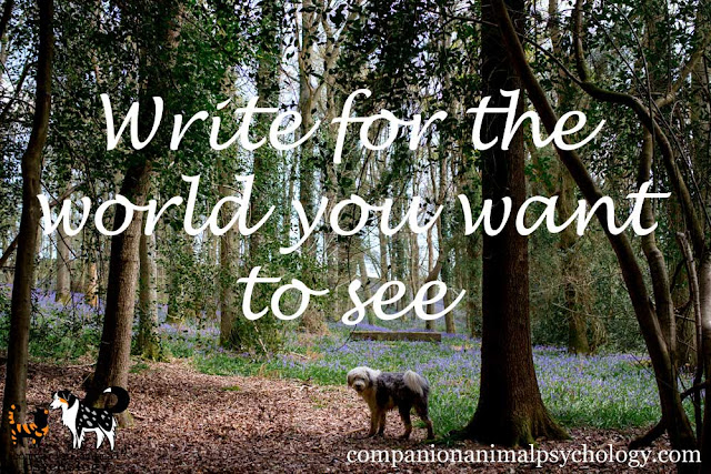 Write for the world you want to see, banner with text over dog in bluebell woods