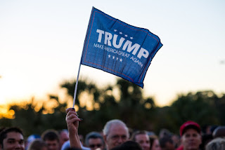Trump supporter waves their flag while in line for the rally at USF in Tampa, FL.