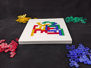 A game in progress. A number of pieces in the various colours have been placed on the board, while the remaining pieces are piled at each corner.