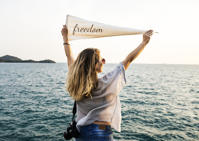 "An image of a millennial woman holding up a piece of cloth with ""Freedom"" written on it. She is facing the ocean."
