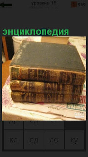 На столе лежат три книги энциклопедии с едва различимым названием
