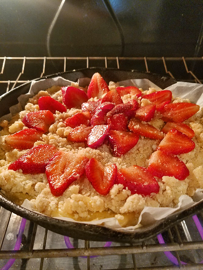 this is a recipe on how to make an old fashioned buttermilk strawberry baked shortcake in a cast iron skillet with streusel topping and it's baking in the oven
