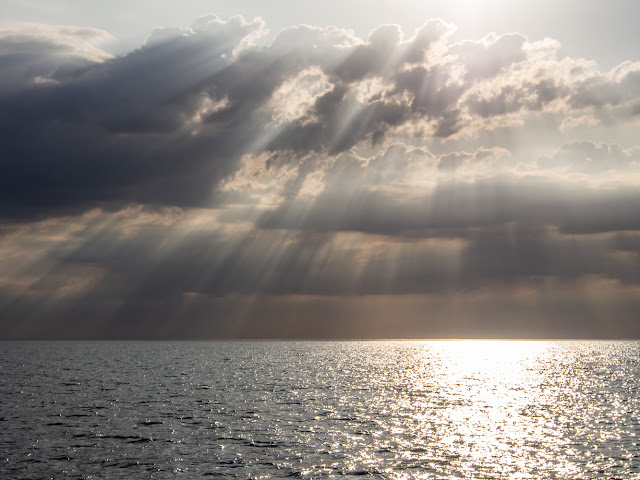 Photo of the sun breaking through heavy clouds over the Solway Firth