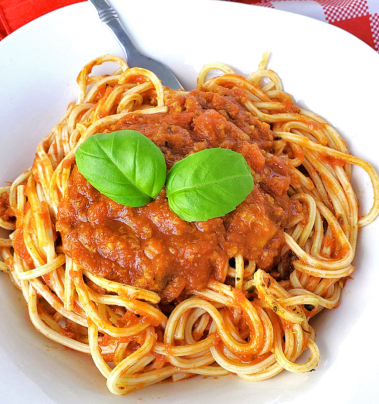 this is pasta with bolognese sauce on top and fresh basil