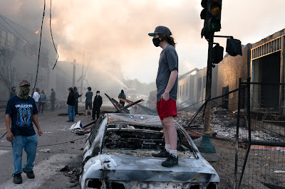 A man stands on a burned out car on Thursday morning as fires burn behind