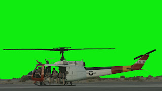 A Huey Helicopterin on the ground with crew in doorway against a green background