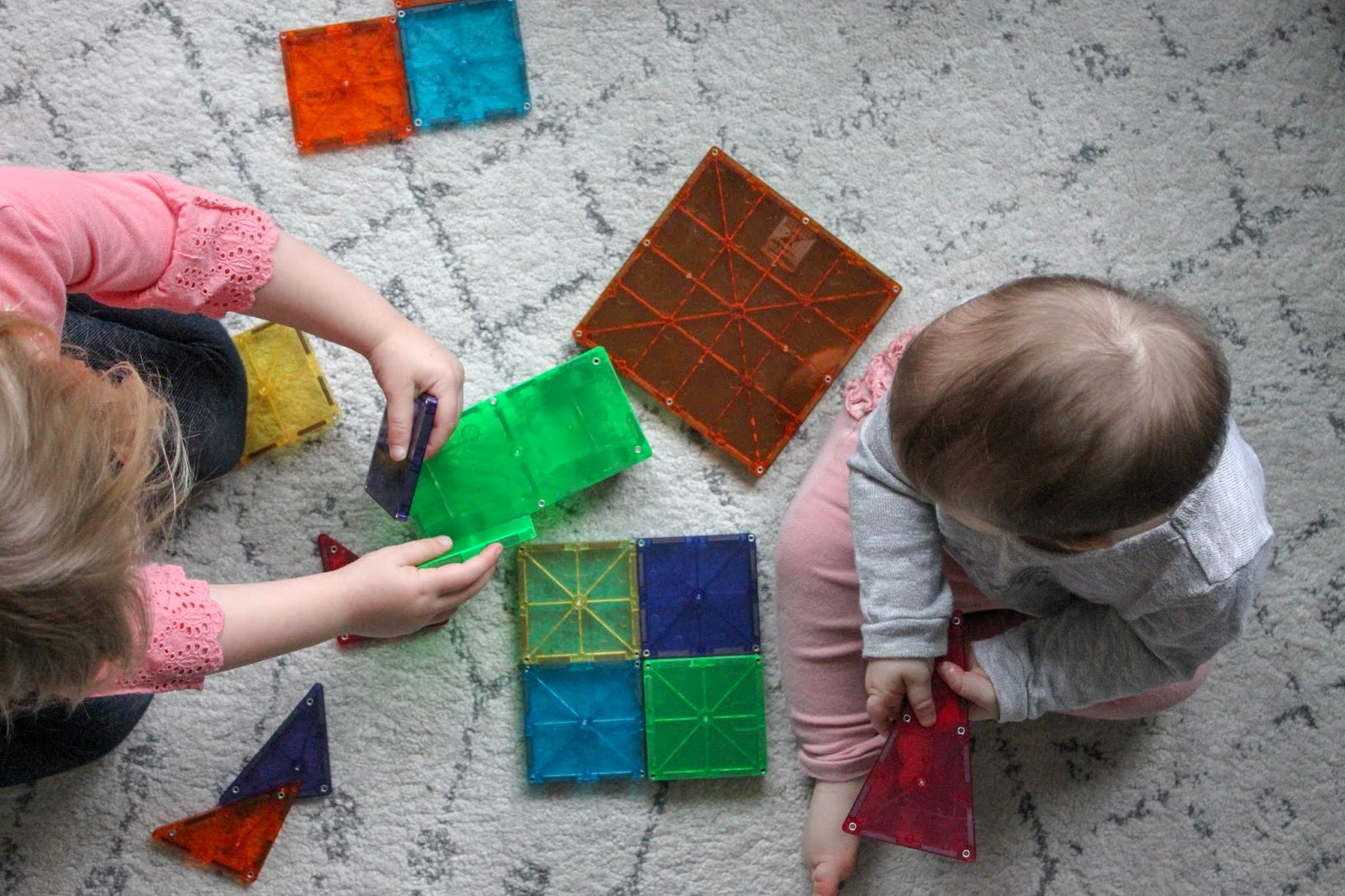 toddler playing with magnetic tiles
