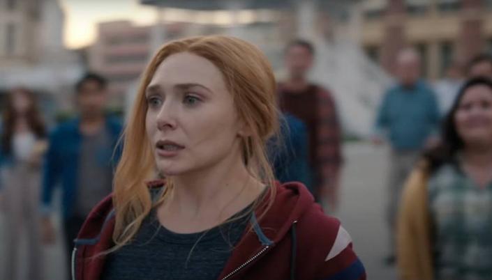 Imagem: Wanda, uma mulher branca de olhos azuis e ruiva com cabelo preso, está amedrontada e cercada de outras pessoas que a encaram. Ela usa um moletom vermelho e uma blusa preta.