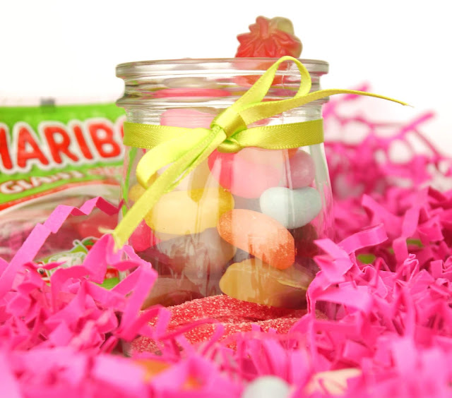 a close up shot of a glass jar filled with strawberry spaghetti, jelly beans, and strawberry shaped sweets