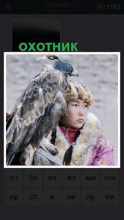 стоит парень с птицей, которая занимается охотой