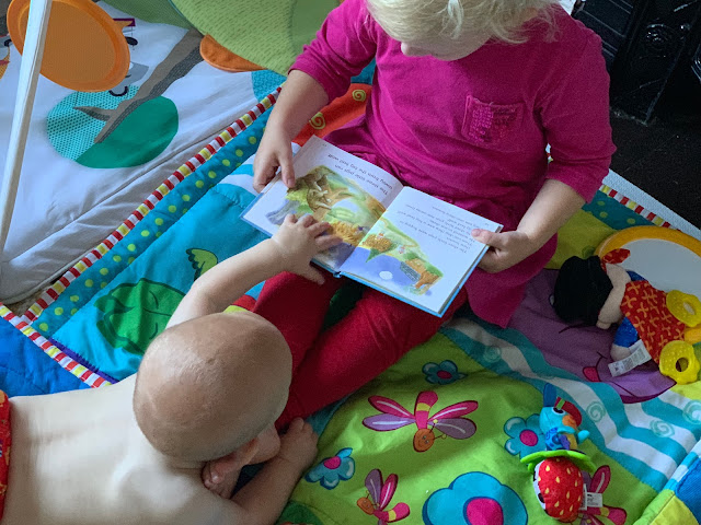 Siblings reading a book, a baby is reaching out for it