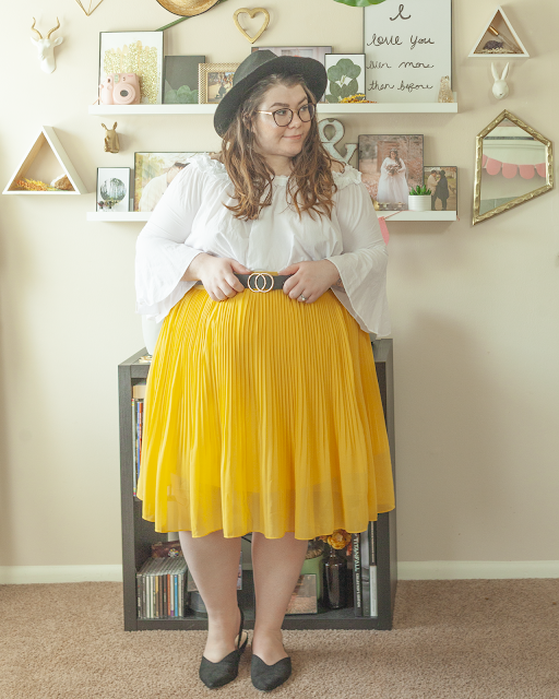 An outfit consisting of a black wide brim hat, a white off the shoulder blouse with bell sleeves tucked into a yellow pleated midi skirt with black pointed toe slingback flats.