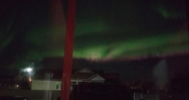 Aurora Borealis aka northern light show seen outside my window dancing in the sky above my neighbors house
