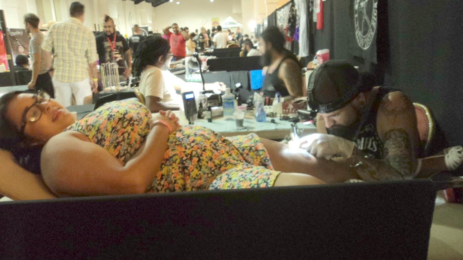 Mujer tatuandose en el ink fest