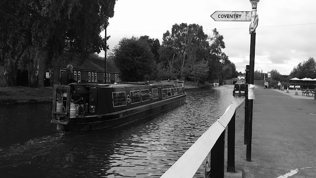 a boat passing a signpost pointing to the coventry canal