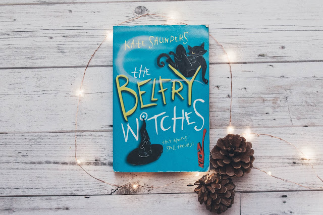 The Belfry Witches by Kate Suanders surrounded by fairlights and pinecones