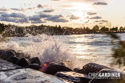 view of waves frozen with a high shutter speed, and backlit by a setting sun