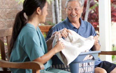Home health aide assisting senior adult with house chores