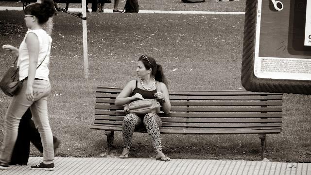 Mujer sentada en banco plaza