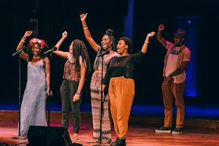 Photo of the 2016 DC Youth Slam Team on stage at the 2016 Brave New Voices International Youth Poetry Slam Festival in DC. The four young women are smiling with one hand raised in a fist as they share their team chant. The Youth Programs coordinator, Joseph Green, is in the background with his hand up too.