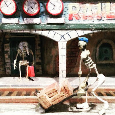 Model skeleton pushing a trolley of baggage at a miniature ghost train.