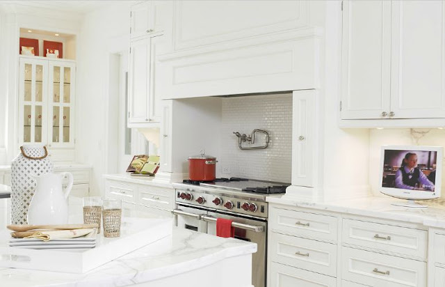 Alternative view of an all white kitchen where you can see the stainless appliances and the subway tile backsplash