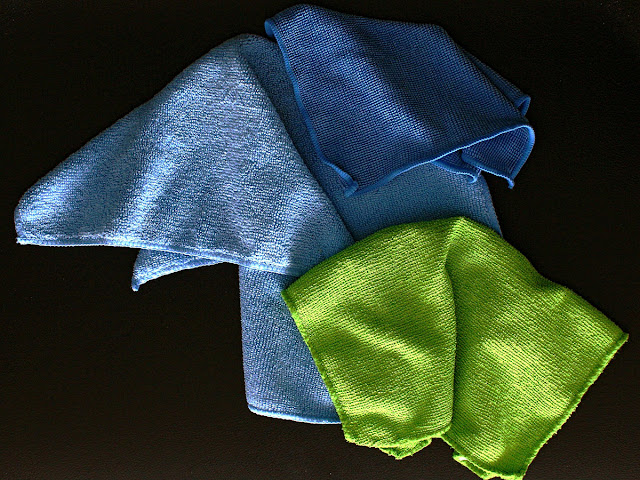 Dark blue, blue, and green microfiber towels on a black table
