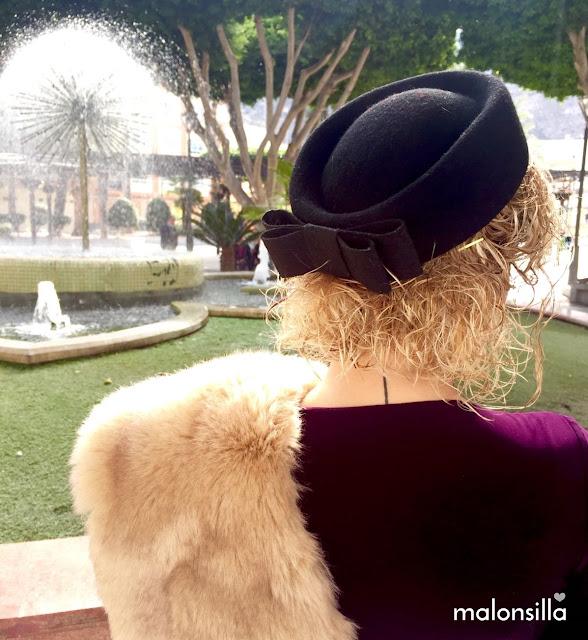 Invitada de invierno de espalda con tocado pillbox en negro, pelo suelto rizado y estola. Vestido color berenjena