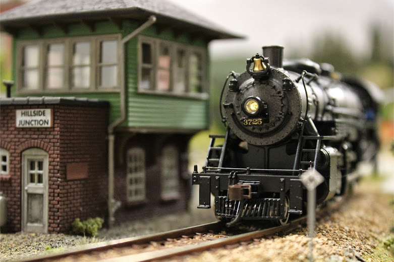 A Broadway Limited USRA Light Mikado 2-8-2 steam locomotive passes in front of a completed Atlas Signal Tower kit