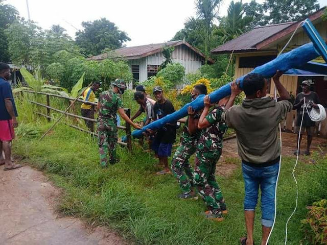 Satgas Yonif 125/Si'mbisa dan Warga Gotong Royong Pasang Tiang Listrik di Kampung Toray