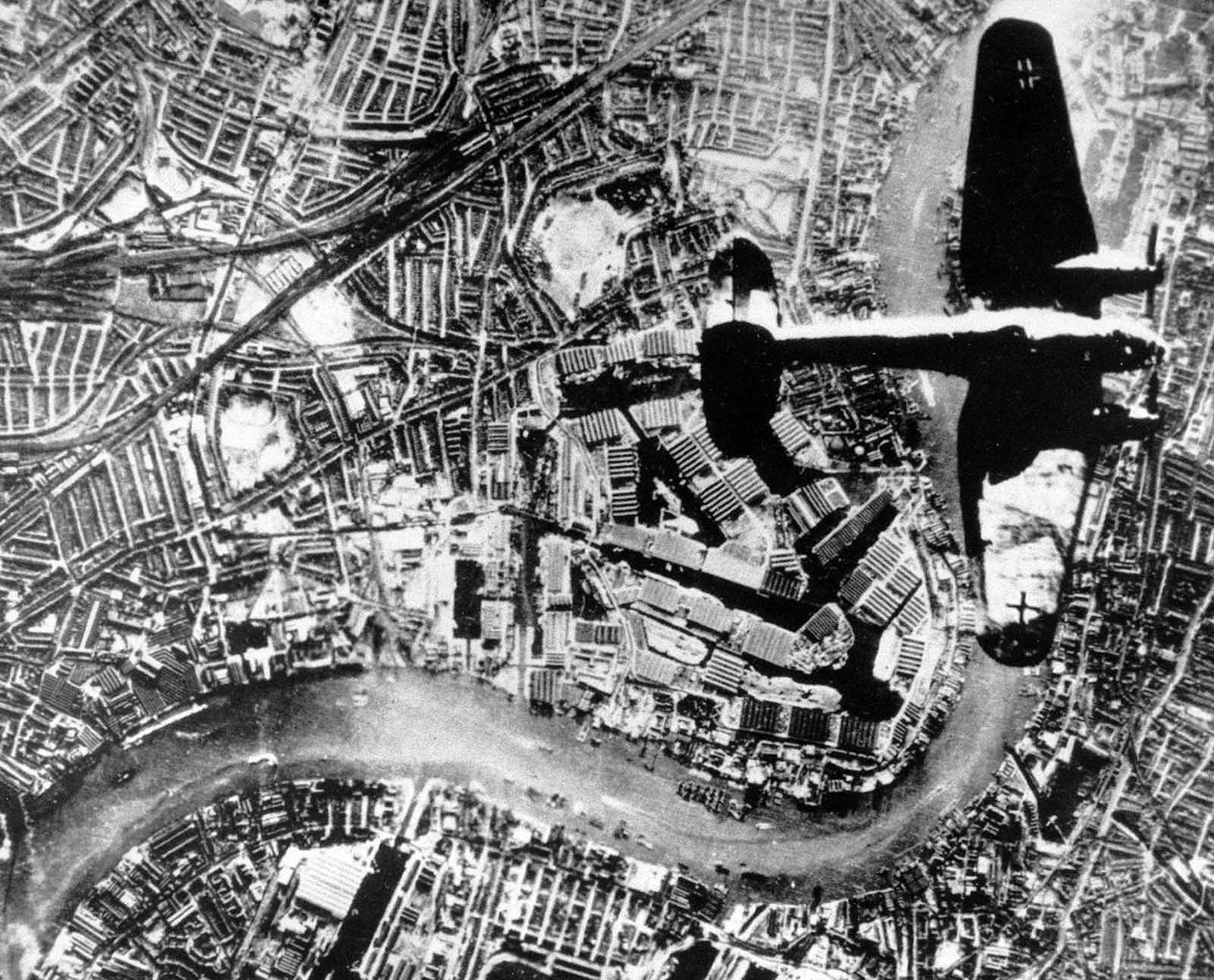 A Nazi Heinkel He 111 bomber flies over London in the autumn of 1940. The Thames River runs through the image.