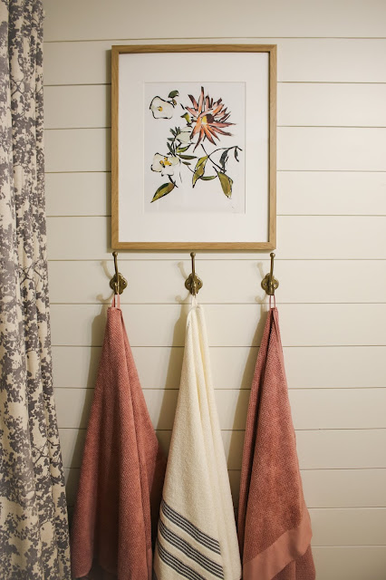 brass towel hooks and art in a bathroom makeover