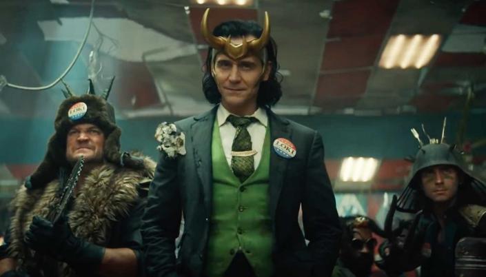 No centro vemos Loki um homem de terno verde com cabelo preto na altura do ombro e ele é branco e sorri maliciosamente. Ele usa um Elmo com chifres dourados e ele tem um botão de eleição na lapela do terno dele. Atrás dele tem dois homens brancos usando casacos de pele e segurando armas e capacetes pontudos e atrás de tudo é um ambiente fechado destruído com placas vermelhas e cinzas no teto.