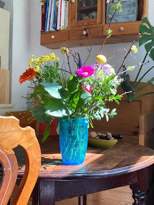 Stuhl, Tisch, Regal, Küchenbank und ein Blumenstrauß