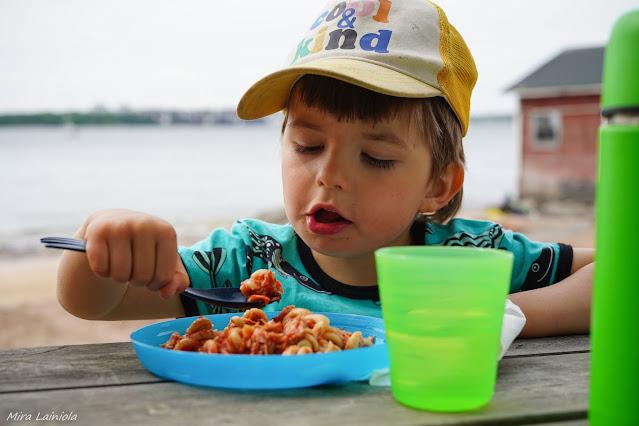 Lapsi syö pastaa eväspöydän ääressä