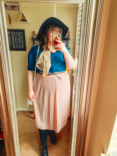 A mirror selfie of an outfit consisting of an oversized black floppy hat, a navy blue short sleeve blouse with a pink lace scarf tied into a bow, and a pink pleated midi skirt.