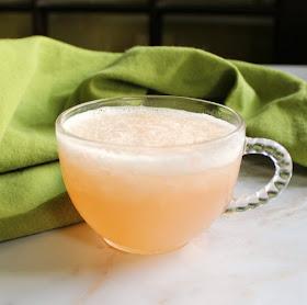 close up of a glass punch mug with slushy peach punch inside