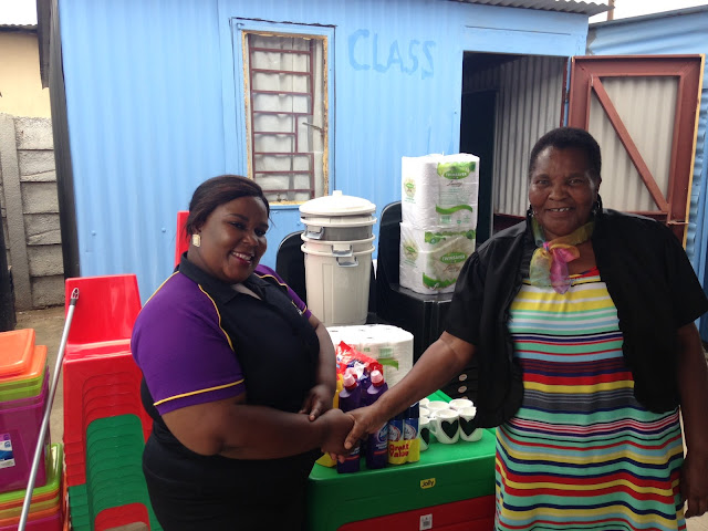 Yvonne from the Hollywoodbets team with Mama Dorah at the Shalate Drop-In Centre. The donations are in the background.