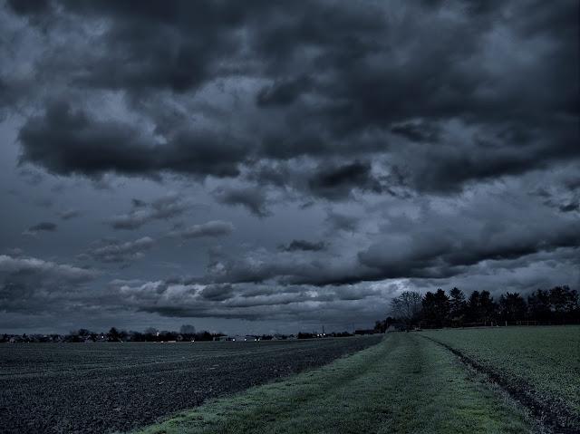 Dunkle Wolken über Leopoldshöhe. Ein Wiesenweg führt durch die Felder.