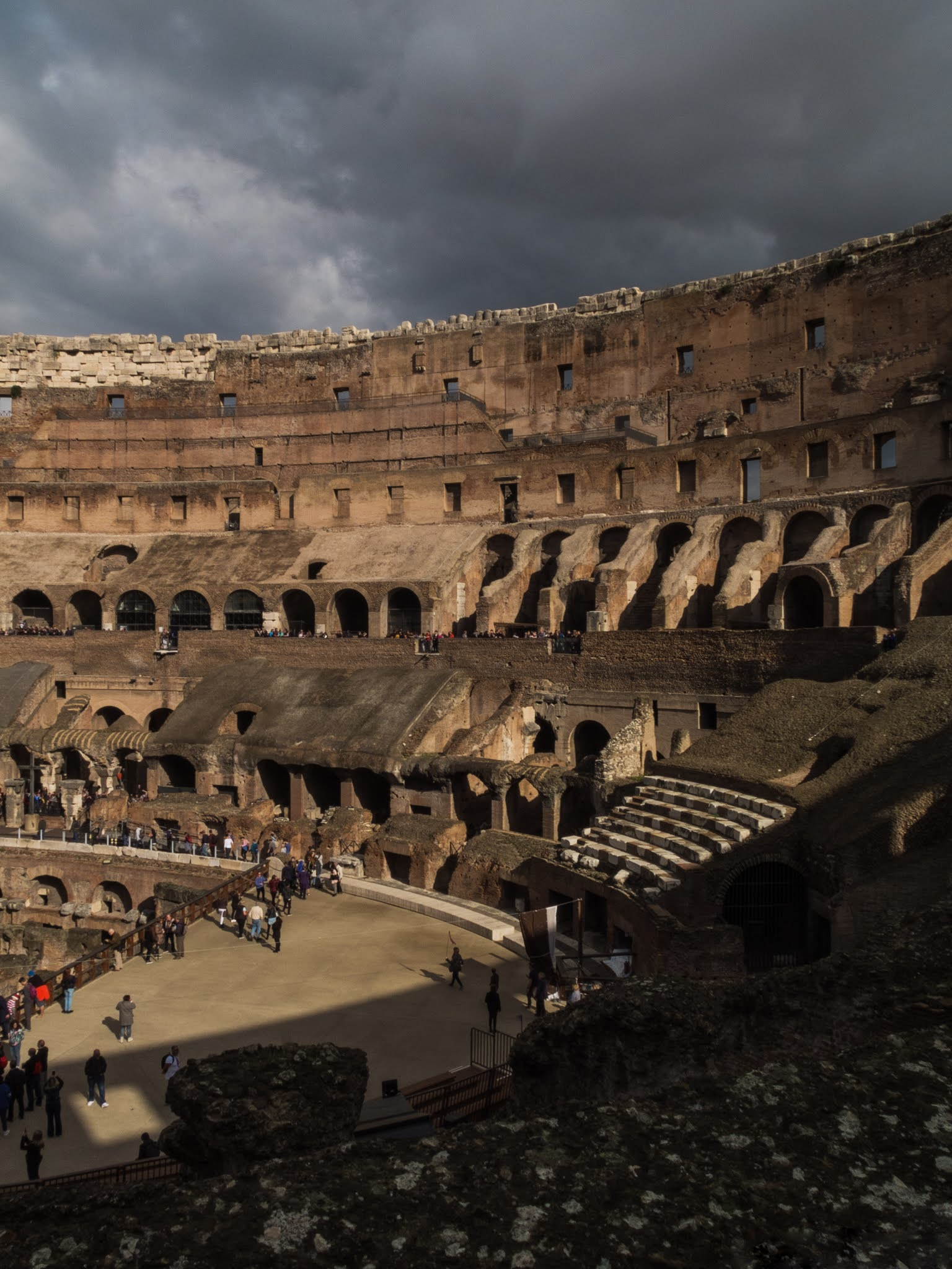 A look inside a sun-lit Colosseum arena with clouds above.