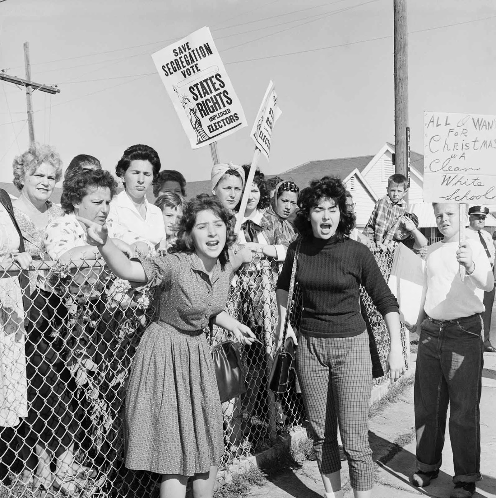 Women at William Franz Elementary School yell at police officers during a protest against desegregation of the school. Some carry signs stating