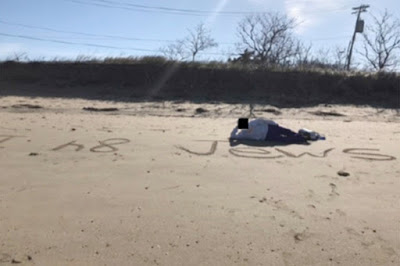 """An MAST student lying on the beach, smiling, next to the words """"I H8 JEWS"""" scrawled in the sand Court document evidence photos"""
